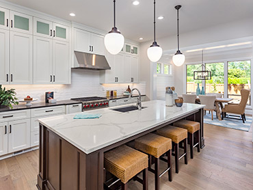 white kitchen with marble island and gas stove