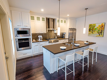 white kitchen with large island and wall oven