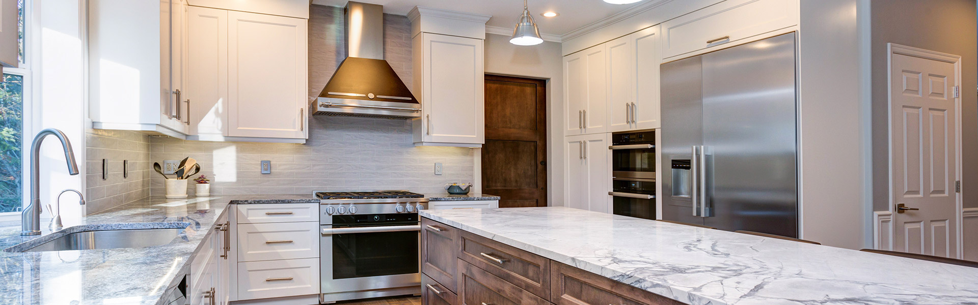 white kitchen with dark island and marble counters