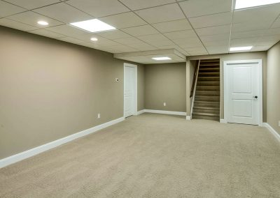 carpeted basement with suspended ceiling