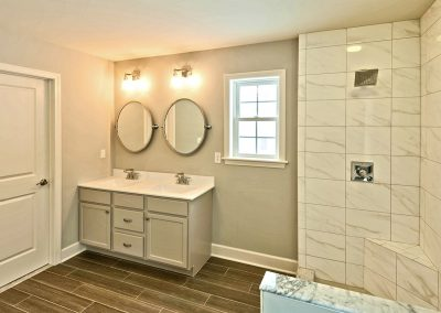 white double vanity with oval mirrors and shower