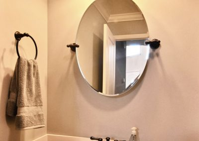 pedestal sink and oval mirror in powder room