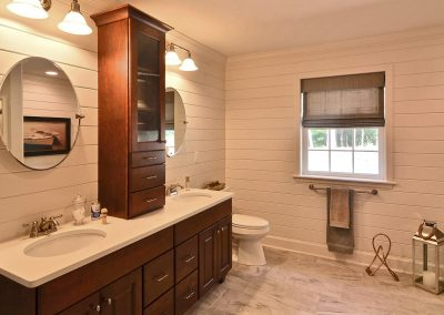 decorative walls with double vanity with upper cabinet and round mirrors