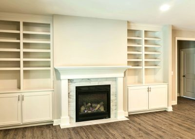 built in shelving and cabinets either side of fireplace