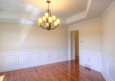dining room with angled walls and tray ceiling