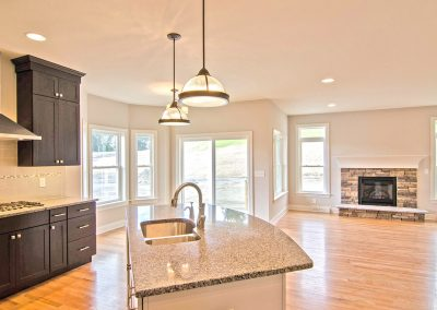 open plan kitchen dining and living with stone fireplace