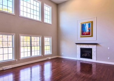 two story room with windows and fireplace