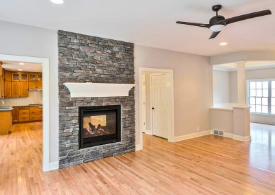 ceiling height stone fireplace and hardwood flooring