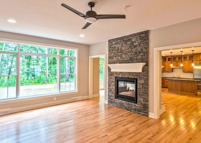 ceiling height stone fireplace with large window