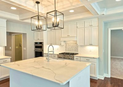 white kitchen with marble counters and coffered ceiling