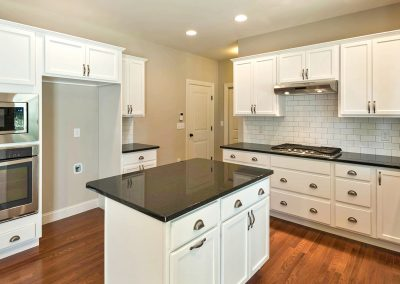 white kitchen dark counters with wall oven
