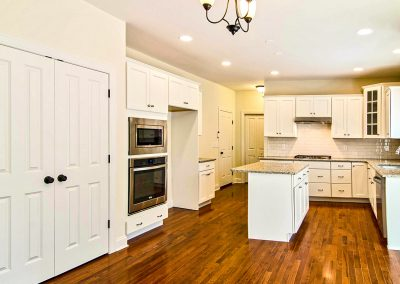white kitchen with island and double door pantry