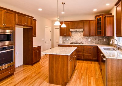 dark kitchen with island and wall oven