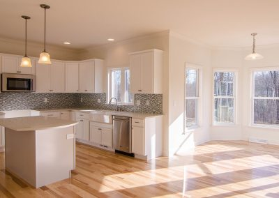 white kitchen with glass tile and breakfast nook