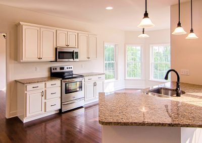 white kitchen with breakfast nook and angled peninsula