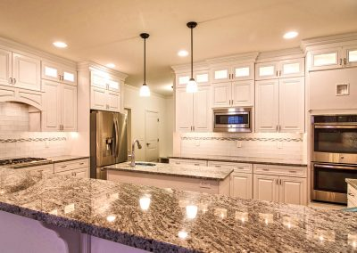 white custom kitchen with prep sink and wall ovens