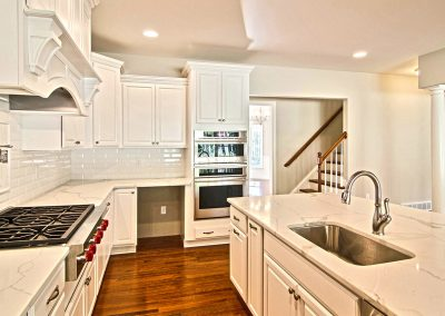 white kitchen with marble counters and gas range