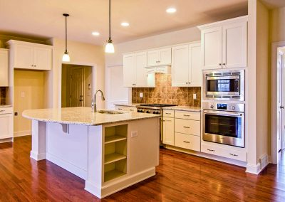 open plan white kitchen with curved island countertop