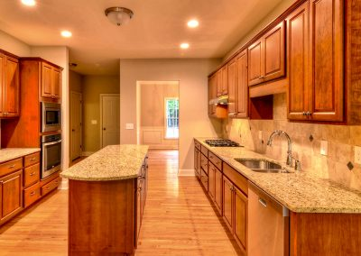 galley style kitchen with center island and wall oven