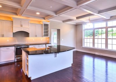 white kitchen with dark counters and coffered ceiling