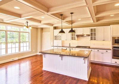 white kitchen with large windows and coffered ceiling