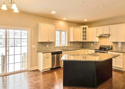 white kitchen with angled island and sliding glass door