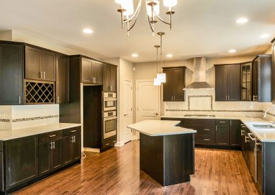dark kitchen with angled island and end cabinets
