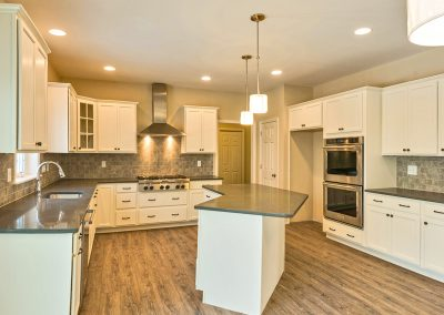 white kitchen with grey countertops and double ovens