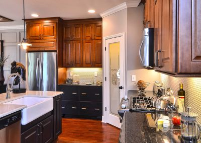 dark kitchen with drawer cabinets and farmhouse sink