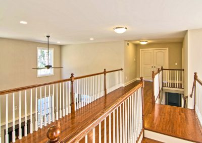 upper landing of dual staircase overlooking foyer and family room