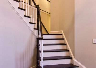 dual staircase with wood railings and spindles