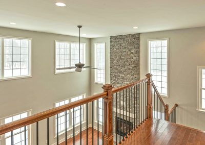 upper landing overlooking family room with iron spindles and wood railings