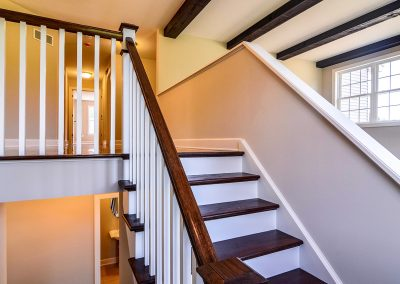 staircase with square wooden railings and half wall