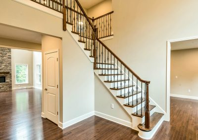 wooden staircase with iron spindles and rounded first step
