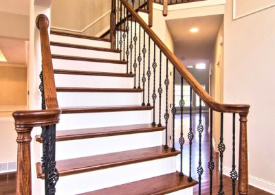 wooden staircase with iron spindles and decorative wall molding