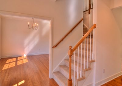 carpeted staircase with wall railing